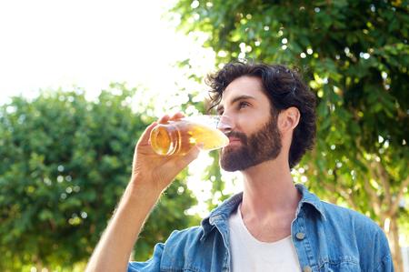 hombre tomando cerveza: Retrato de un apuesto joven bebiendo cerveza al aire libre