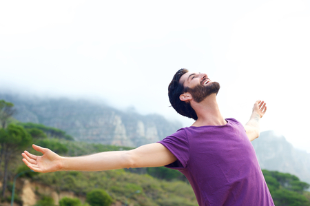 man arm: Portrait of a happy carefree man smiling with arms open outdoors Stock Photo