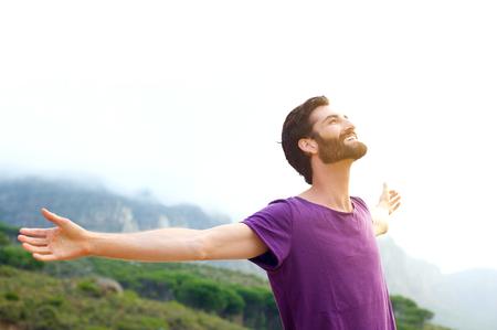 両手を自然に立って幸せな若い男の肖像を広げ