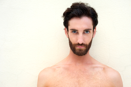 model posing: Close up portrait of a young shirtless sexy man with beard