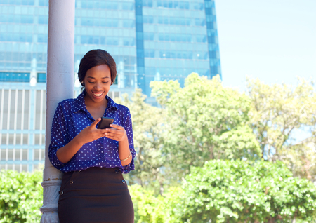 smart girl: Young business woman reading text message on mobile phone outdoors Stock Photo