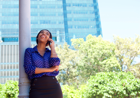 woman speaking: Young business woman laughing on cell phone outside office building