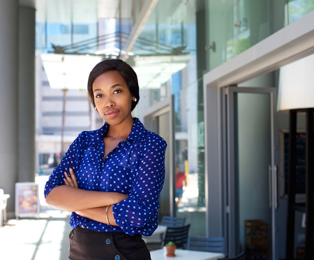 serious: Portrait of a female office worker standing outside business building