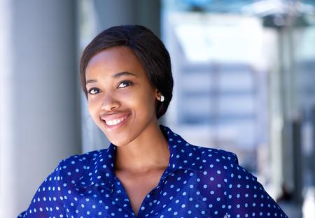 mujer sola: Close up retrato de una mujer de negocios joven amistosa de pie fuera del edificio de oficinas Foto de archivo