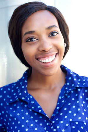 real people: Close up portrait of a cheerful young african american woman smiling