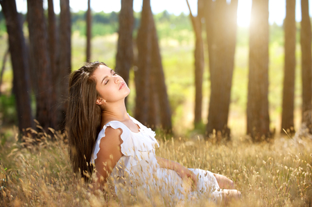 Portrait of a dreamy young woman sitting in field with sunlight in background Stock Photo