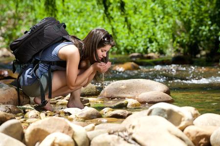 若い女性は、彼女の手で屋外のストリームから水を飲む