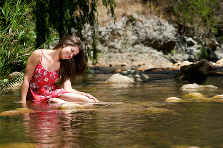 wet dress: Portrait of a happy girl sitting in water with red dress Stock Photo