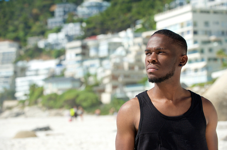 Close up portrait of a handsome young man in black shirt standing at the beach photo