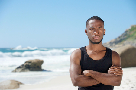 Portrait of a handsome young man standing at the beach with arms crossed photo
