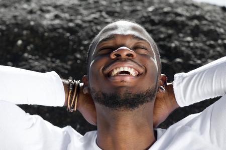 Close-up portret van een vrolijke jonge man buitenshuis lachen met de handen achter het hoofd Stockfoto