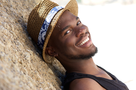 Close up portrait of a smiling young man with hat relaxing outdoors photo