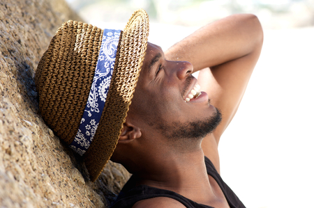 Close up portrait of a cheerful young man laughing at the beach with hat photo