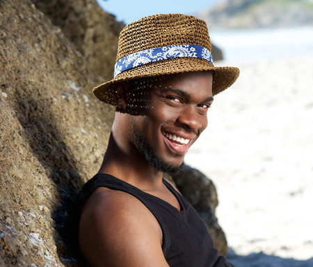 Close up portrait of a cool guy smiling at the beach with hat photo