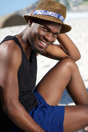 Close up portrait of a relaxed young man smiling at the beach photo