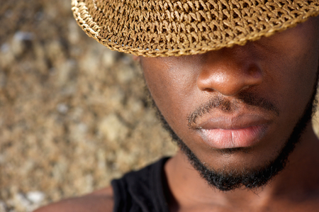 suave: Close up portrait of a young man with hat covering face