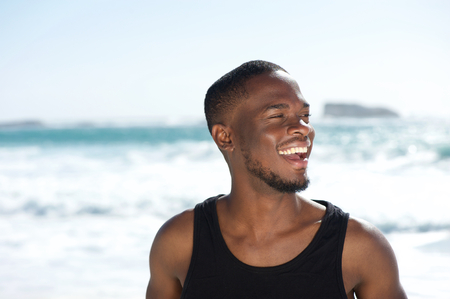 Close up portrait of a handsome young african american man laughing at the beach photo