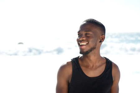 Close up portrait of a happy smiling young man standing at the beach photo