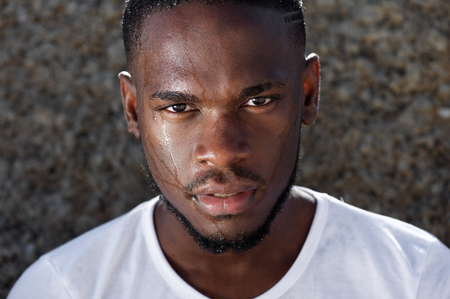 wet men: Close up portrait of a young african american man with sweat dripping down face