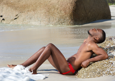 nude pose: Portrait of a sexy young black man sitting by water on the beach Stock Photo