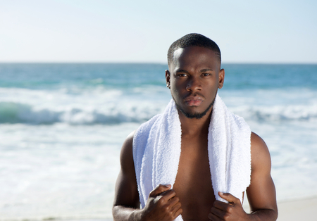 Close up portrait of a handsome young african american man standing at the beach with towel photo