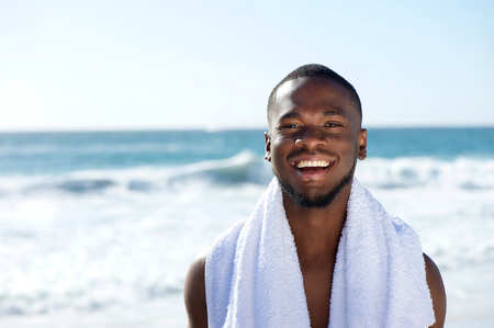 Close up portrait of a happy man smiling with towel at the beach photo