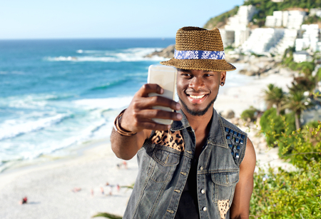 hombres negros: Retrato de un hombre afroamericano guapo sonriendo y tomando Autofoto mientras estaba de vacaciones en la playa