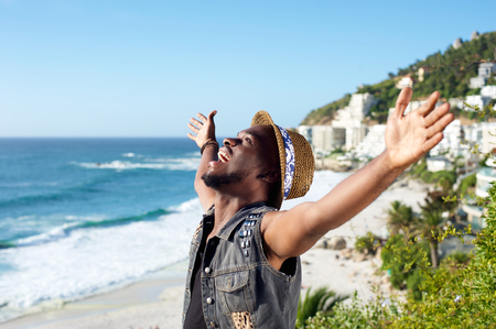 expression: Portrait of a happy african american man with arms outstretched by the beach