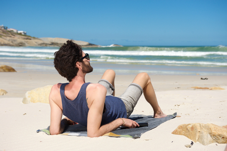 man looking at sky: Rear portrait of a young man sitting alone at a secluded beach on vacation Stock Photo