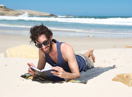 Portrait of a happy young man reading book at the beach photo