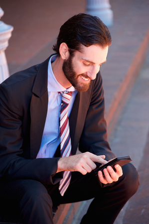 Portrait of a businessman sitting outside and reading text message on mobile phone photo