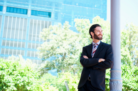 alone person: Close up portrait of a handsome businessman smiling in the city Stock Photo