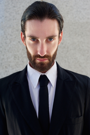 Close up portrait of a cool male fashion model with beard posing in black suit and tie photo