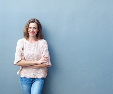 Portrait of a happy mid adult woman smiling with arms crossed on gray background Stock Photo