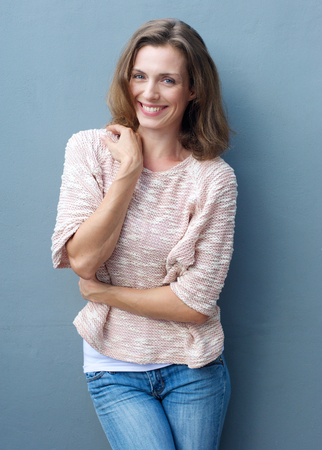 mujeres maduras: Retrato de una alegre mujer de mediana edad que sonríe en pantalones vaqueros y suéter