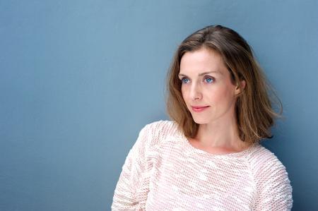 파란색 배경에 포즈 스웨터에 매력적인 여자의 초상화를 닫습니다