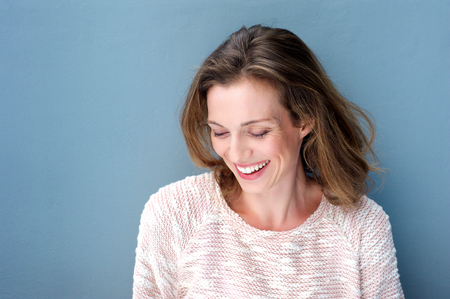 people laughing: Close up portrait of a beautiful mid adult woman laughing with sweater