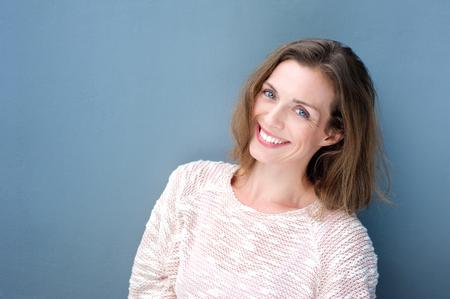 파란색 배경에 매력적인 미소 중반 성인 여자의 초상화를 닫습니다 스톡 콘텐츠