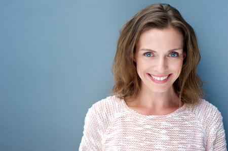 vrouwen: Close-up portret van een mooie oudere vrouw die lacht met trui op een blauwe achtergrond