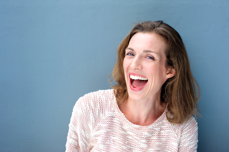 Close up portrait of a happy beautiful fresh mid adult woman laughing on blue background