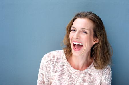Close-up portret van een gelukkig mooie frisse medio volwassen vrouw lachend op een blauwe achtergrond