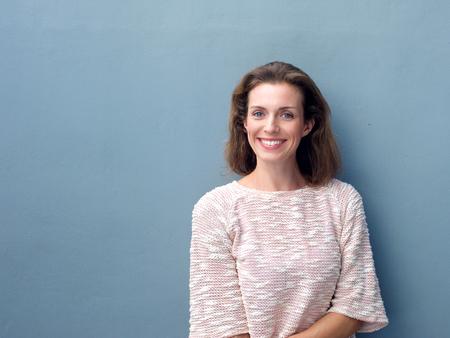 파란색 배경에 미소 아름 다운 중반 성인 여자의 초상화