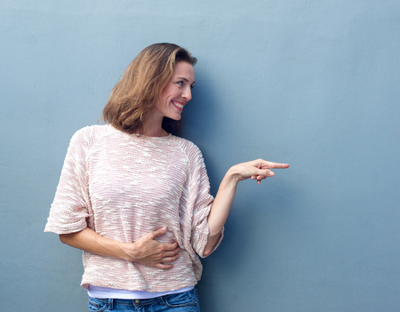 미소하고 공간 복사 손가락을 가리키는 아름 다운 중반 성인 여자의 초상화