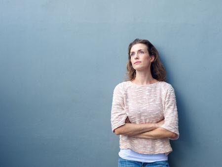 zbraně: Portrét atraktivní ženy pózují s rukama zkříženýma koukal s zamyšleným výrazem Reklamní fotografie