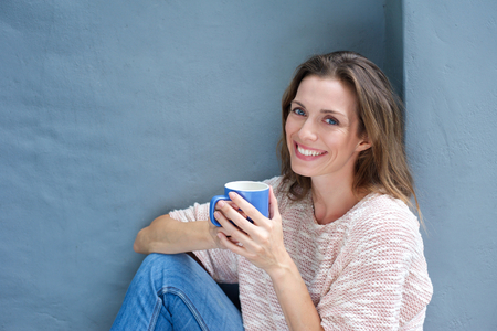 Portrait of a beautiful woman enjoying a drink of a coffee