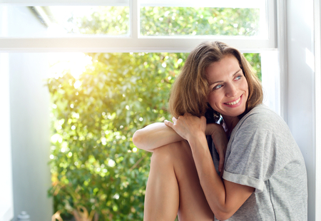 Portrait of a happy mid adult woman sitting by window at home. Relaxed woman smiling Banco de Imagens - 37864548
