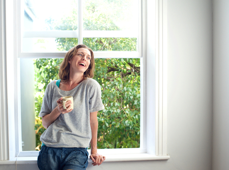 Portrait of a happy woman laughing with a cup of coffee at home photo