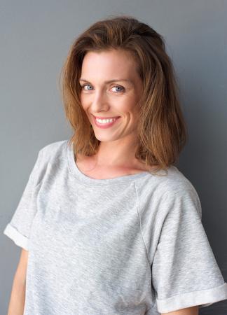 Close-up portret van een mooie medio volwassen vrouw lachend op een grijze achtergrond Stockfoto