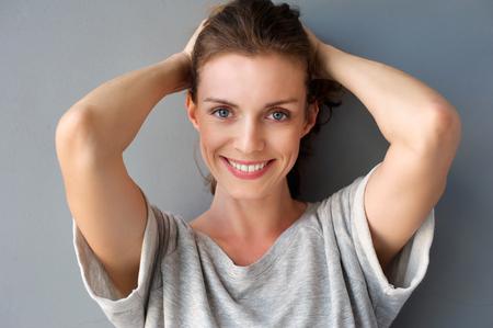 회색 배경에 대해 머리에 손을 웃 고 행복 중반 성인 여자의 초상화를 닫습니다