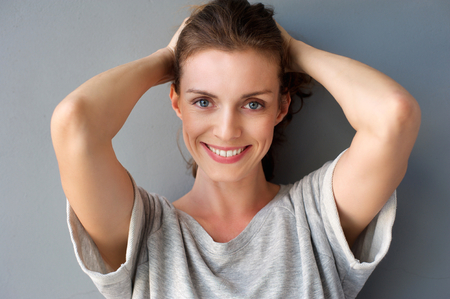 Close up portrait of a happy mid adult woman smiling with hands in hair against gray background Stock Photo